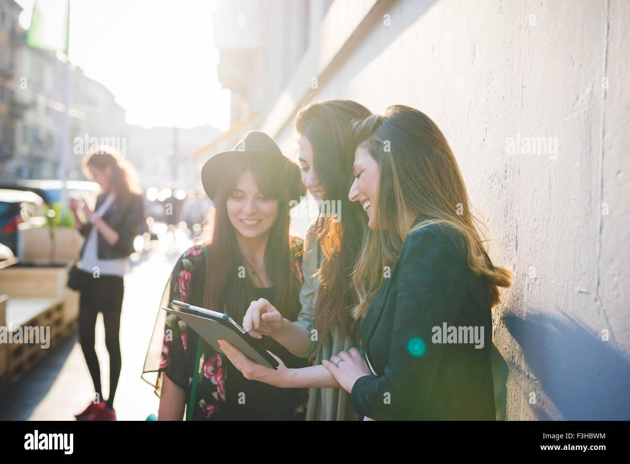 Three young women using digital tablet on city street Stock Photo