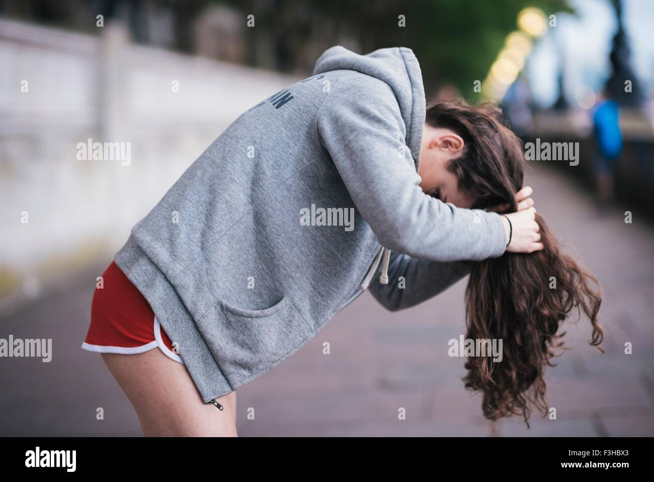 Young female runner tying up long hair on riverside - Stock Image