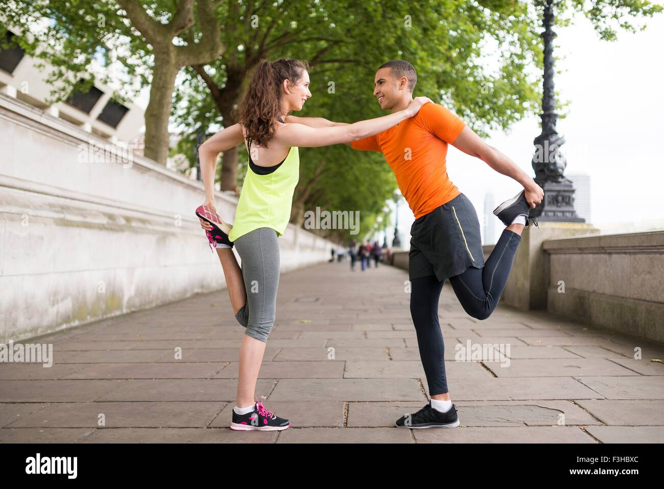 Male and female city runners warming up - Stock Image