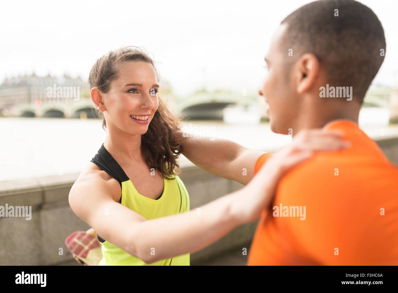 Young male and female runners warming up at riverside - Stock Image