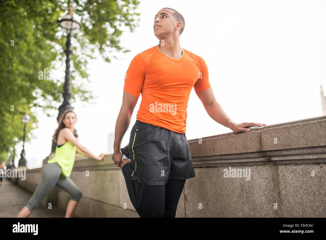 Young male and female city runners warming up - Stock Image
