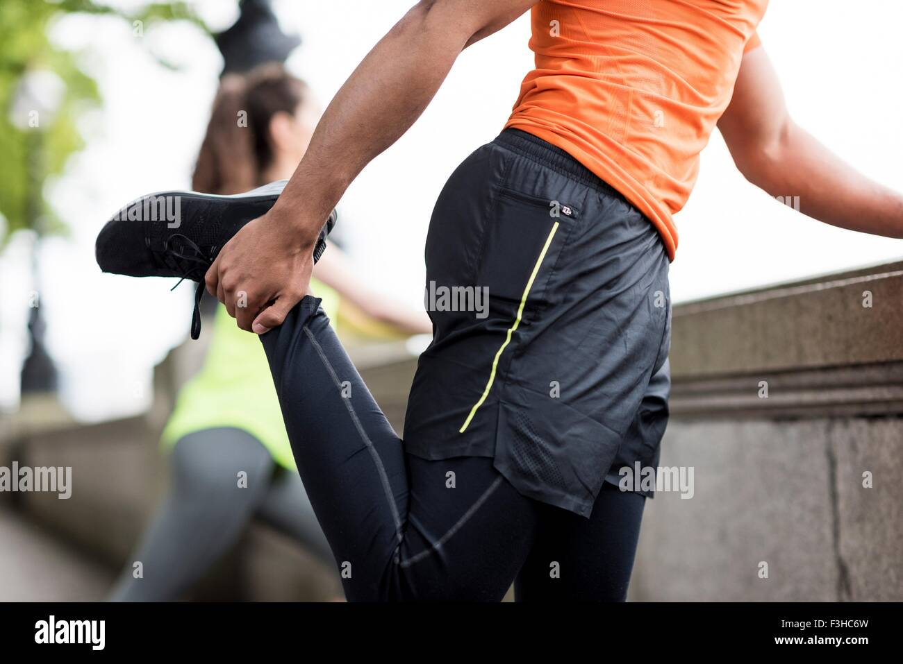 Male and female city runners stretching legs - Stock Image