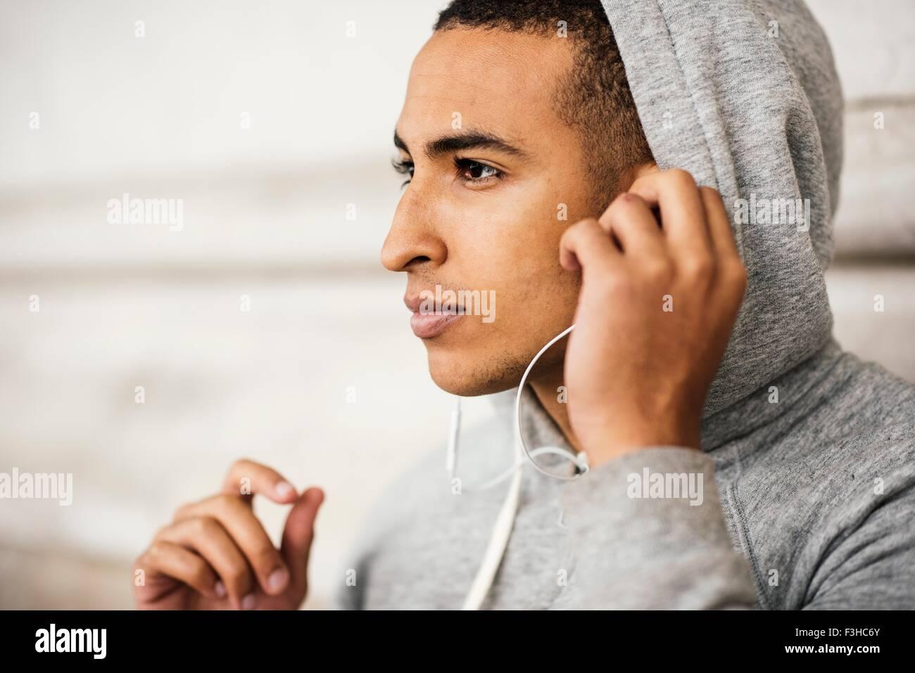 Male runner wearing grey hoody listening to earphone music - Stock Image