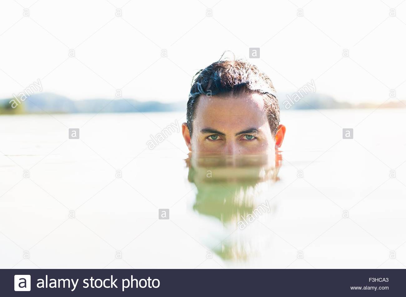 Portrait of young man with face submerged in lake, Woerthsee, Bavaria, Germany - Stock Image