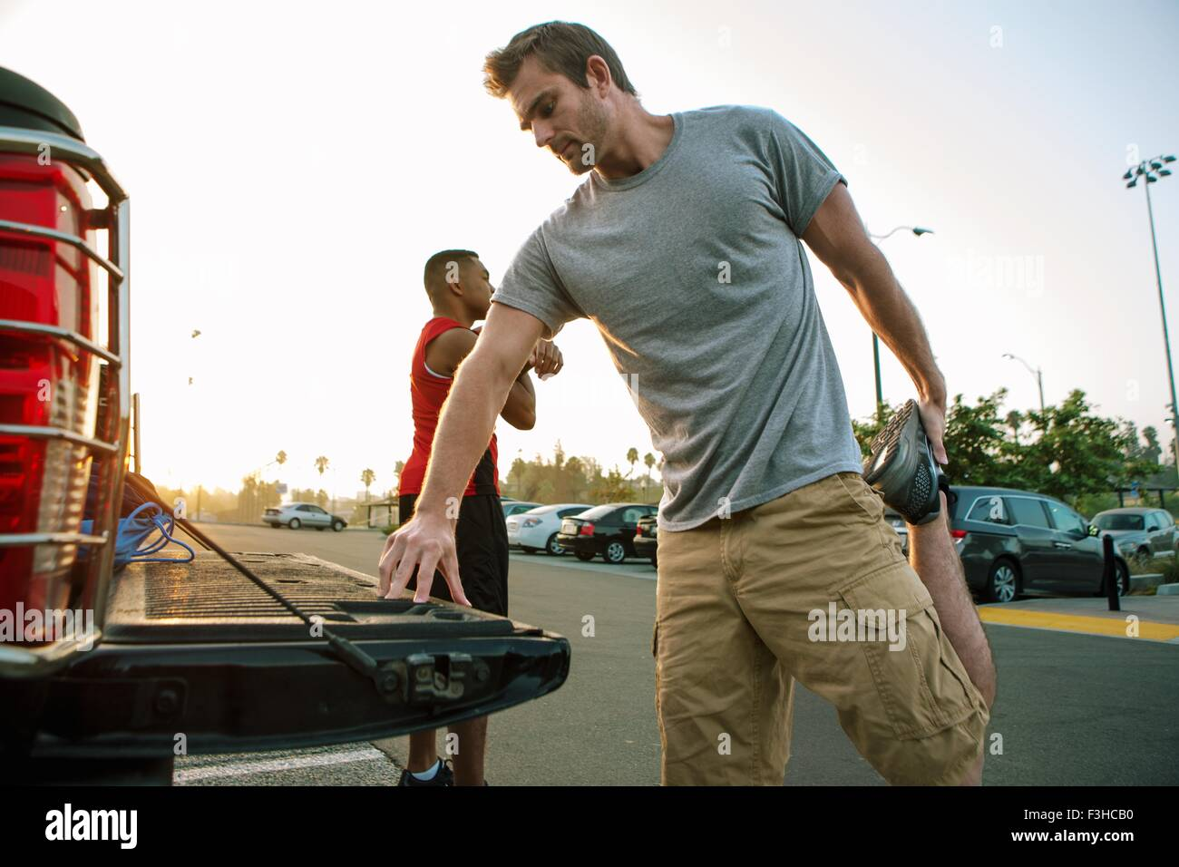 Two male friends, stretching, getting ready for workout - Stock Image