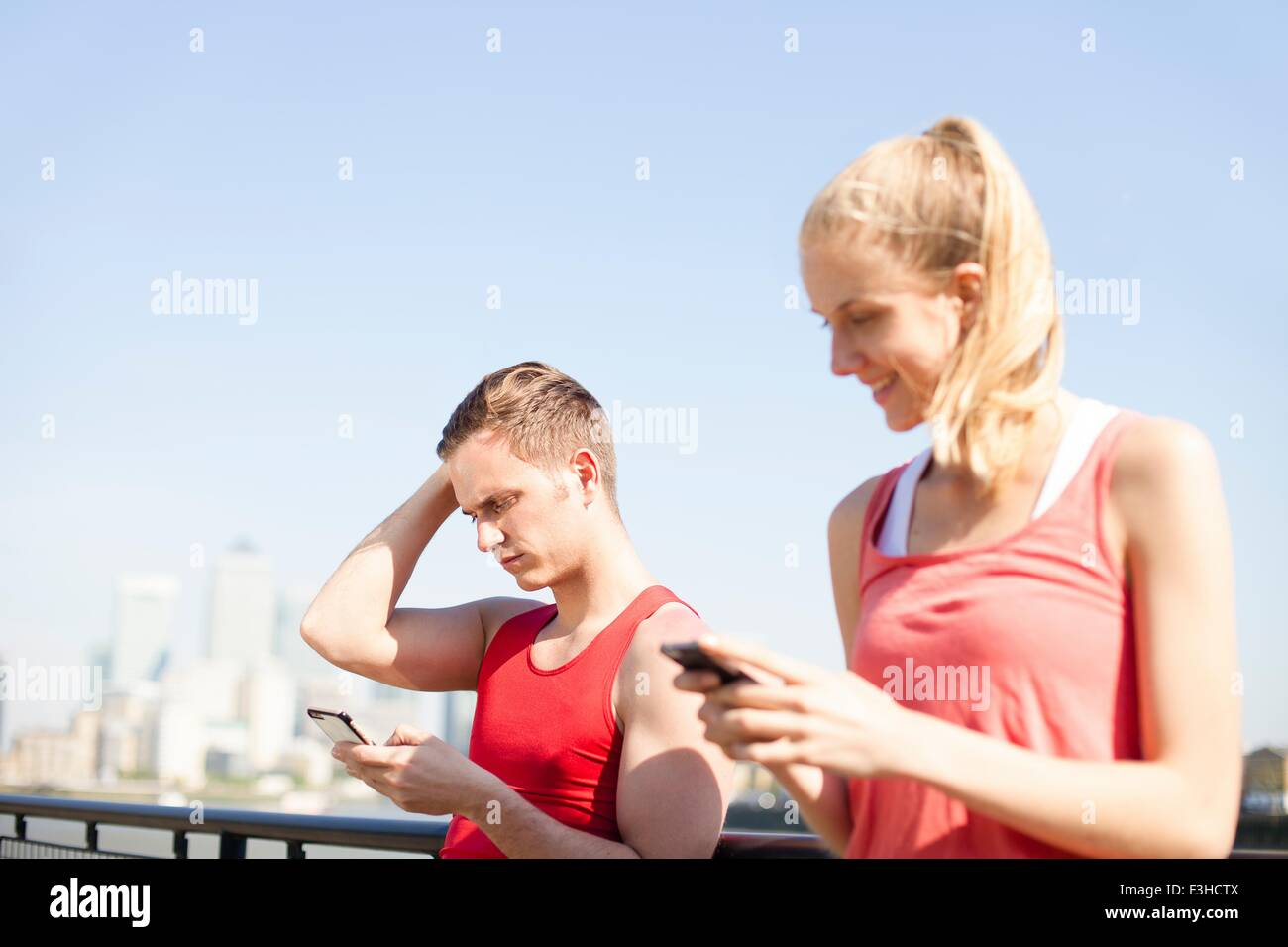 Runners using smartphone on bridge - Stock Image