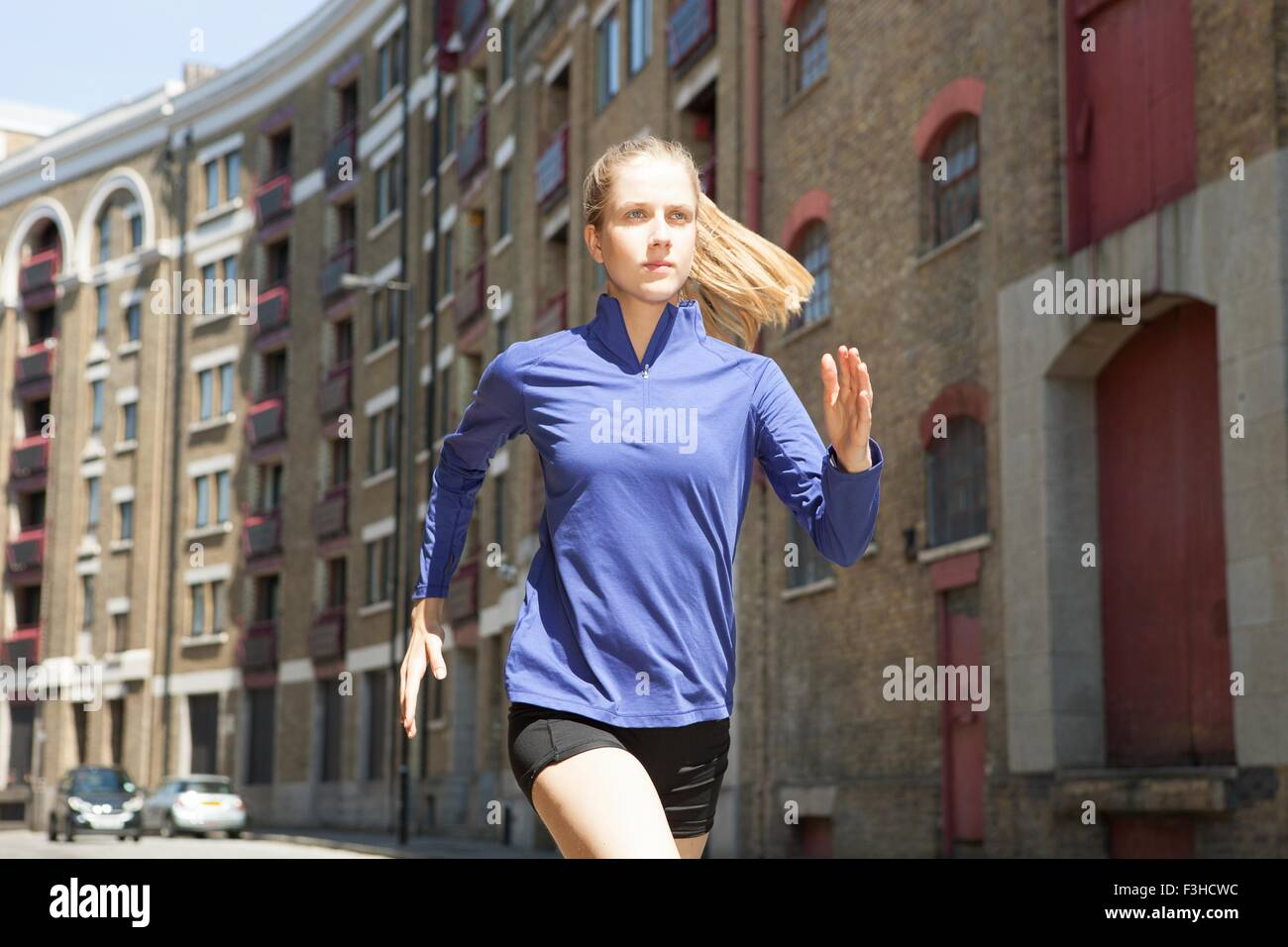 Runner jogging past building block, Wapping, London - Stock Image