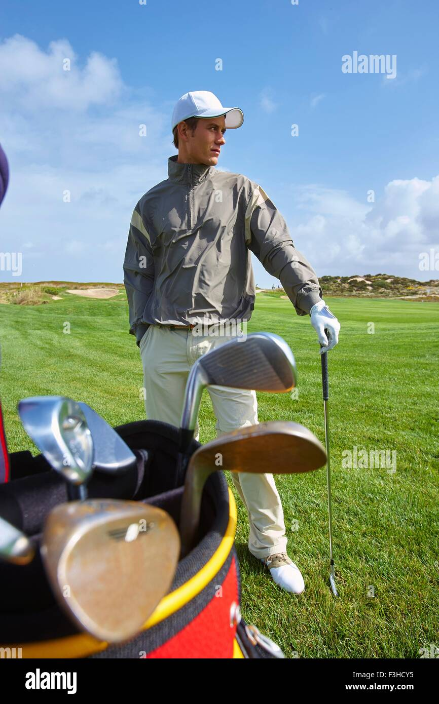 Golfer holding gold club, hand in pocket, looking away - Stock Image