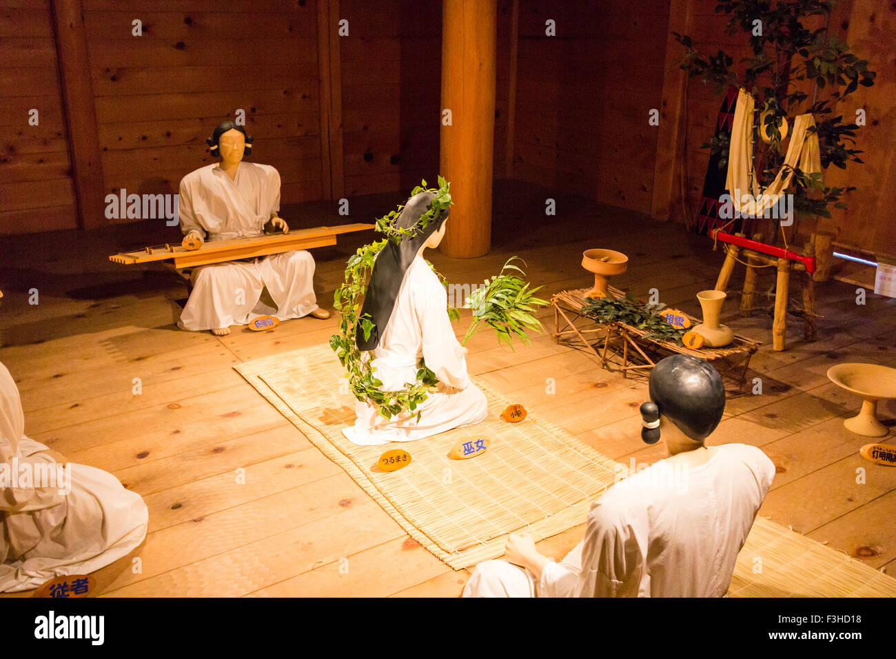 Yoshinogari Park. Yayoi settlement. Kitanaikaku, ceremonial Hall, ritual with girl decked with leaves in fertility - Stock Image