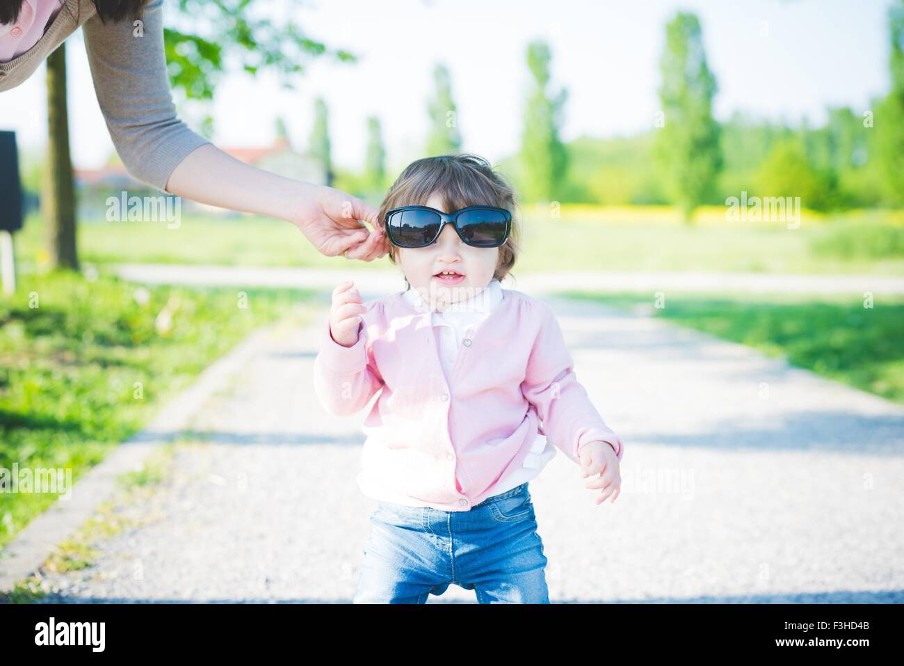 Portrait of female toddler wearing sunglasses in park - Stock Image