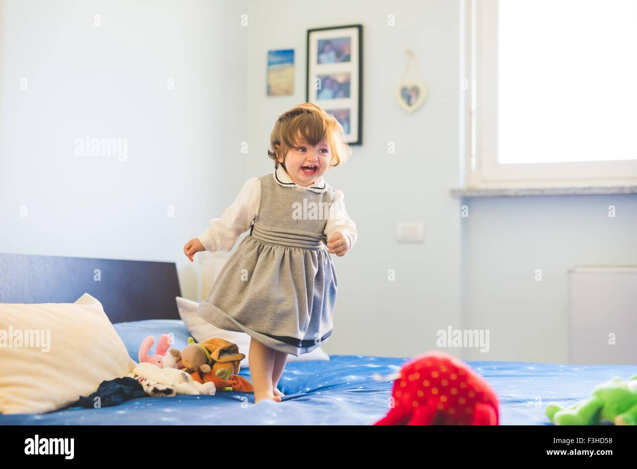 Cute female toddler toddling on bed - Stock Image