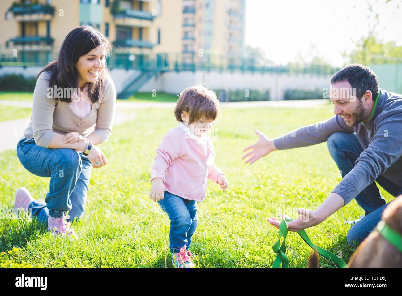 Mid adult couple with toddling toddler daughter in park - Stock Image