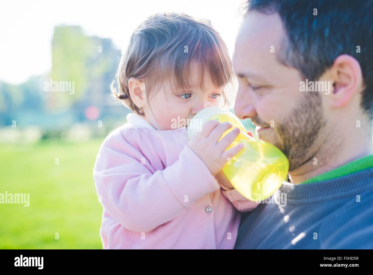Female toddler with father drinking baby bottle in park - Stock Image
