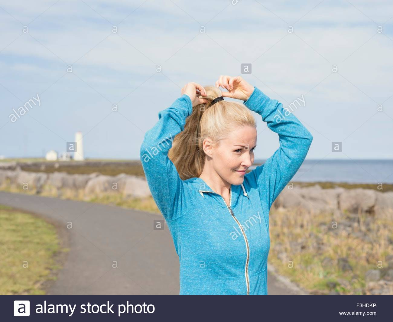 Female runner tying pony tail at coast - Stock Image