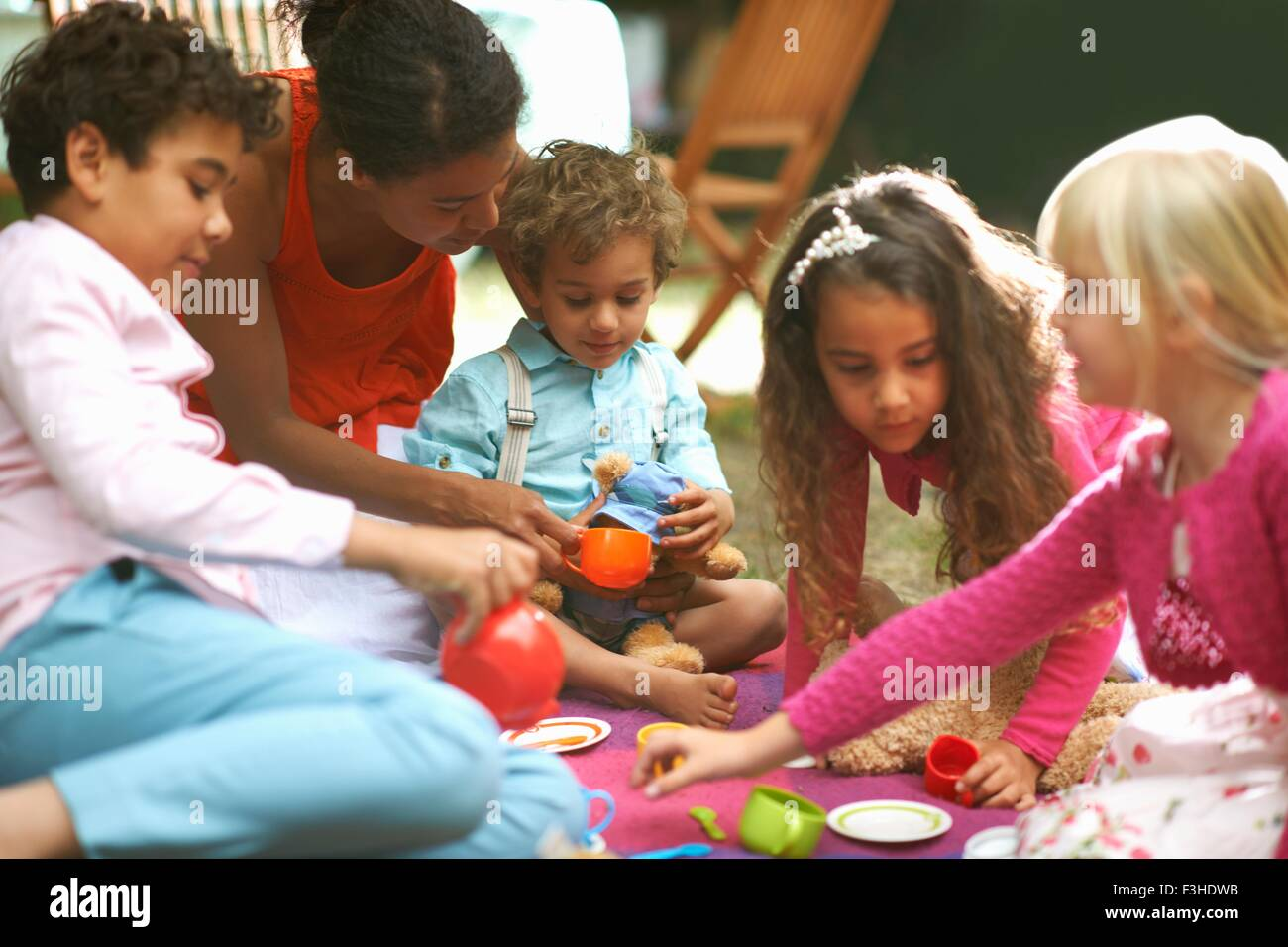 Mother and four children playing picnics at garden birthday party Stock Photo