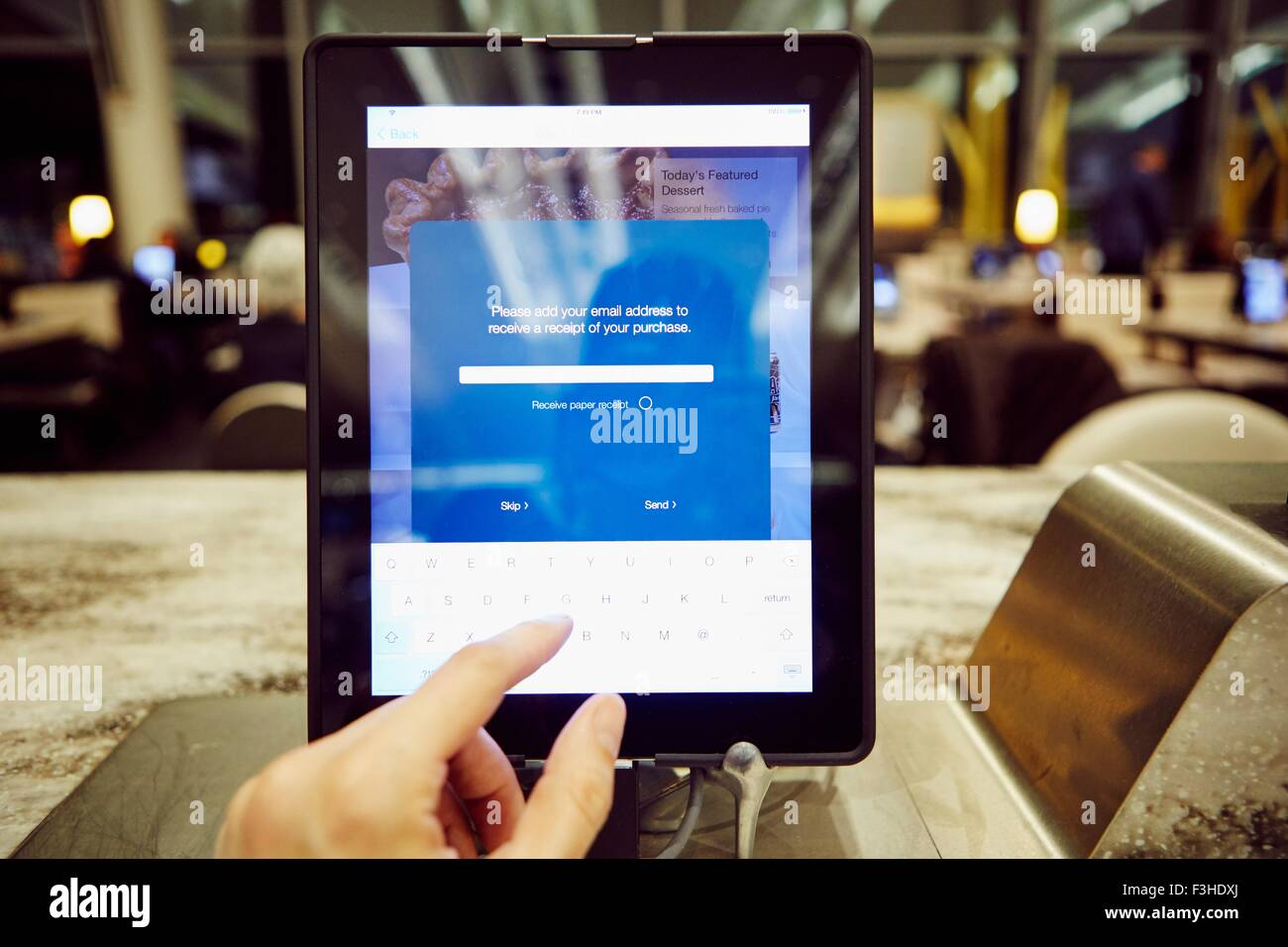 Womans hand using digital tablet touchscreen for restaurant  payment - Stock Image