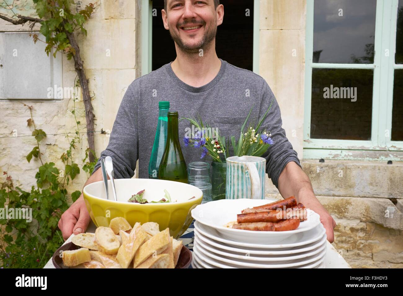 Man carrying tray of food outside house - Stock Image
