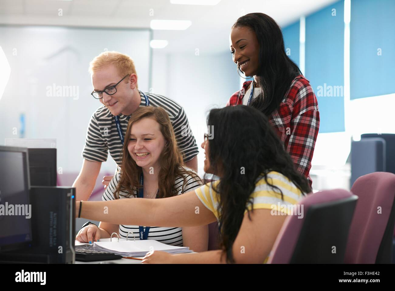 Teacher and students working together in computer class - Stock Image