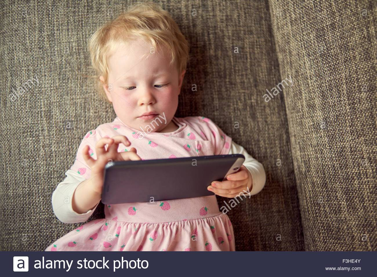 Young girl lying on sofa, holding digital tablet - Stock Image