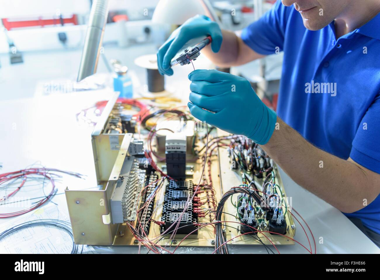Worker assembling electronics in electronics factory - Stock Image