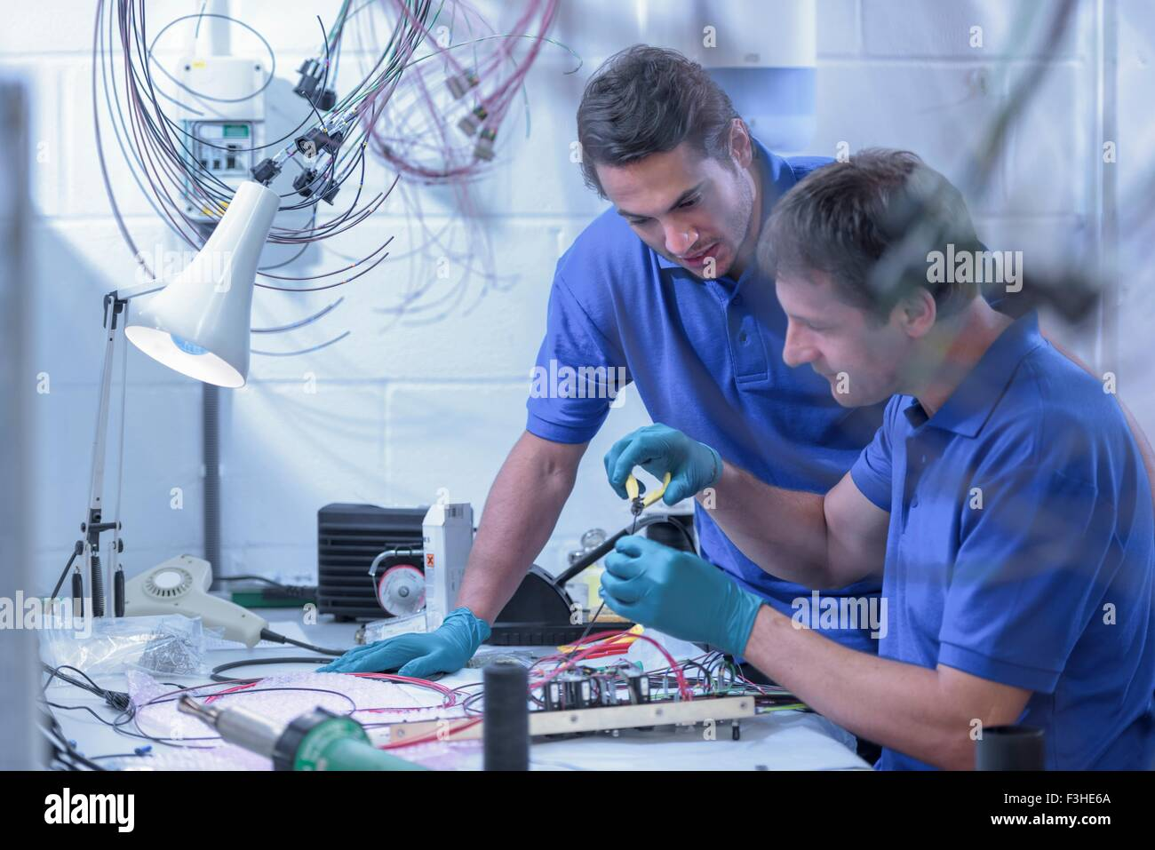 Two male workers assembling electronics in electronics factory - Stock Image