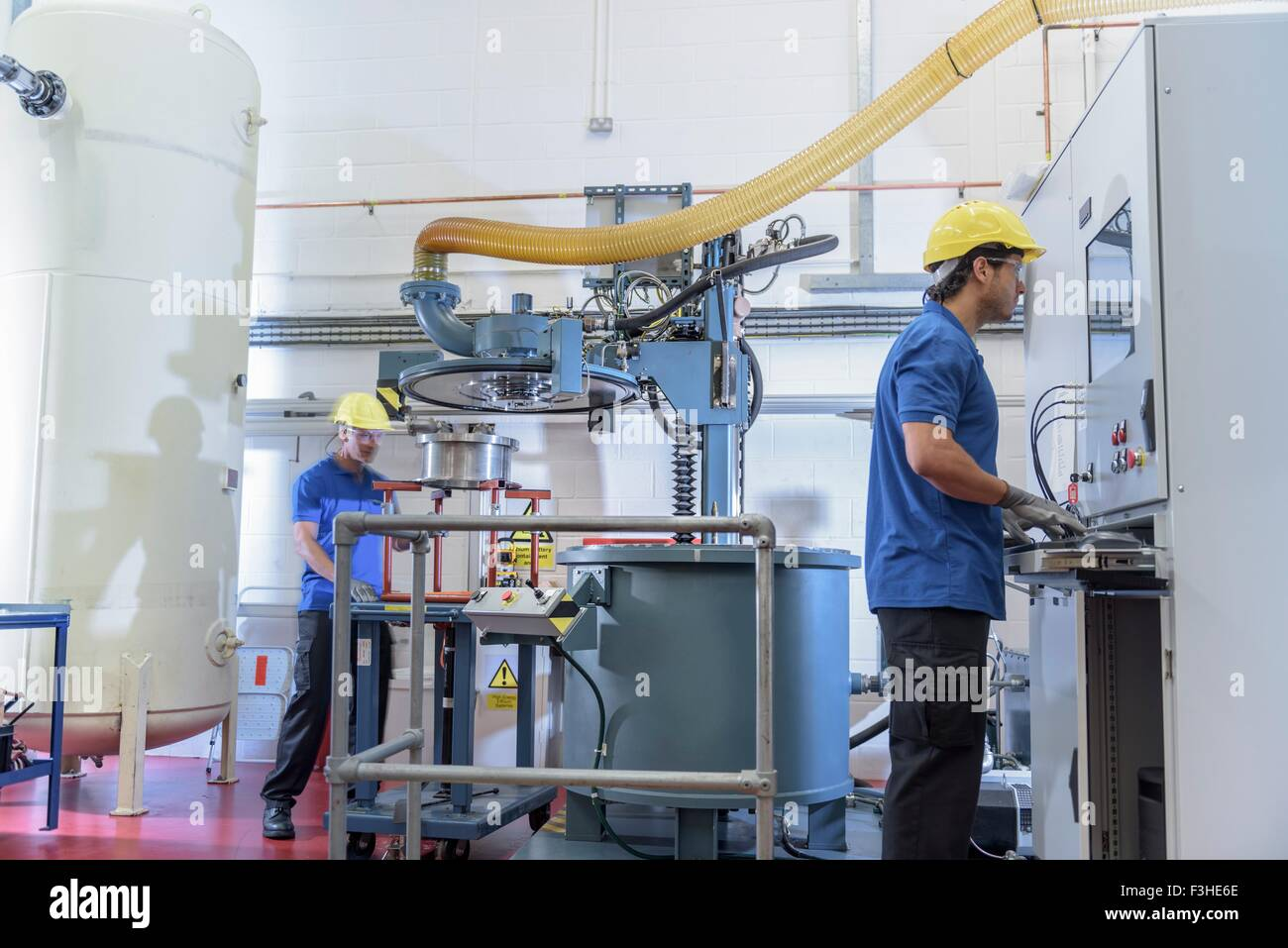 Workers operating environmental testing equipment in electronics factory - Stock Image