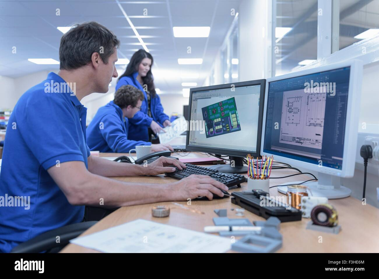 Electronics designers with CAD imagery in electronics factory - Stock Image