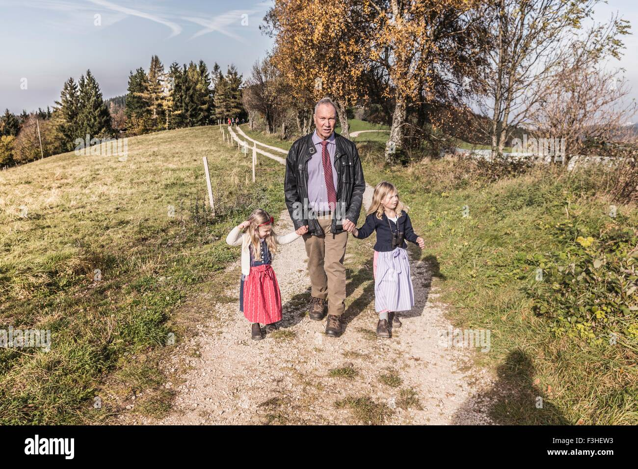 Grandfather strolling on dirt track with two granddaughters, Achenkirch, Austria - Stock Image