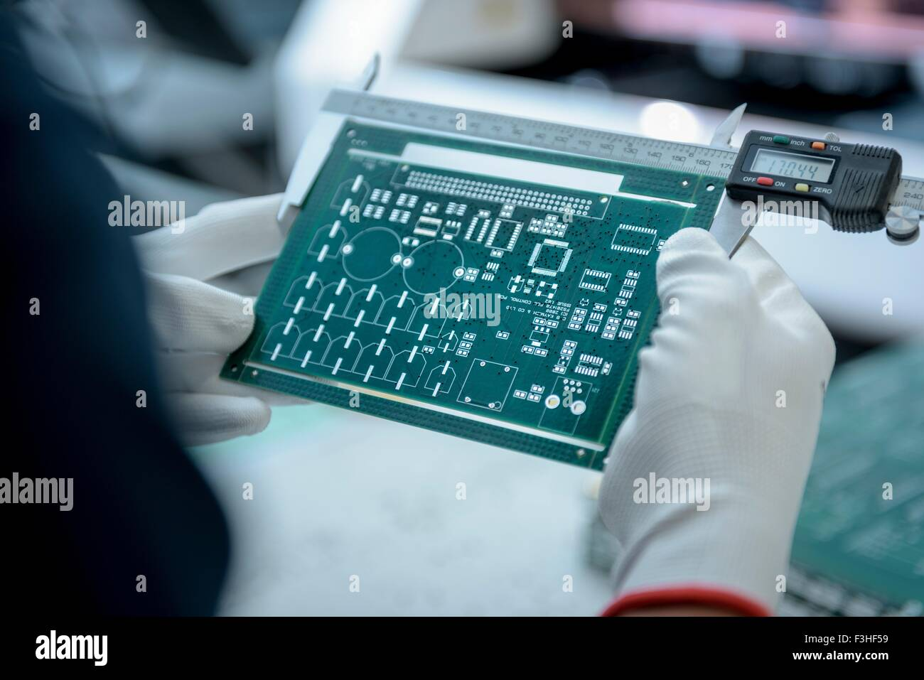 Worker measuring cut circuit board in circuit board factory, close up - Stock Image