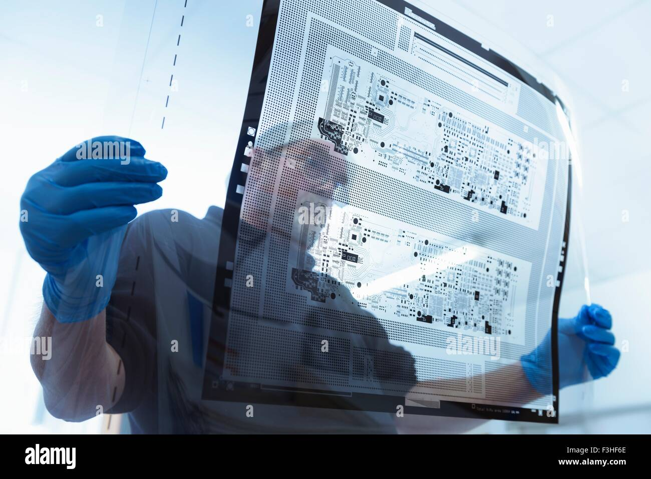 Worker inspecting circuit board negative sheet in circuit board factory - Stock Image