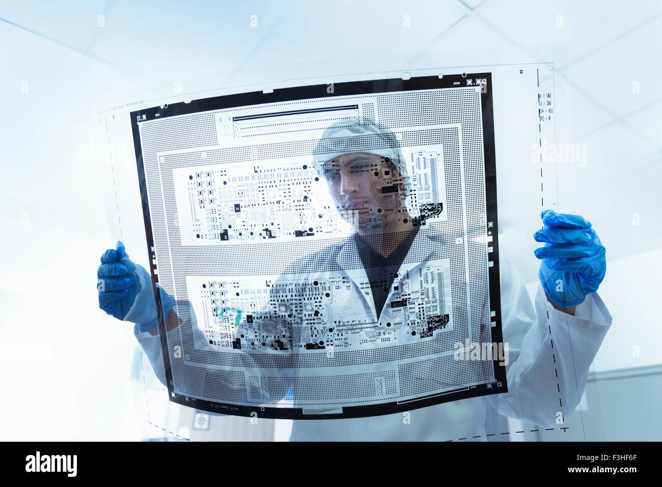 Worker inspecting circuit board negative sheet in circuit board factory Stock Photo