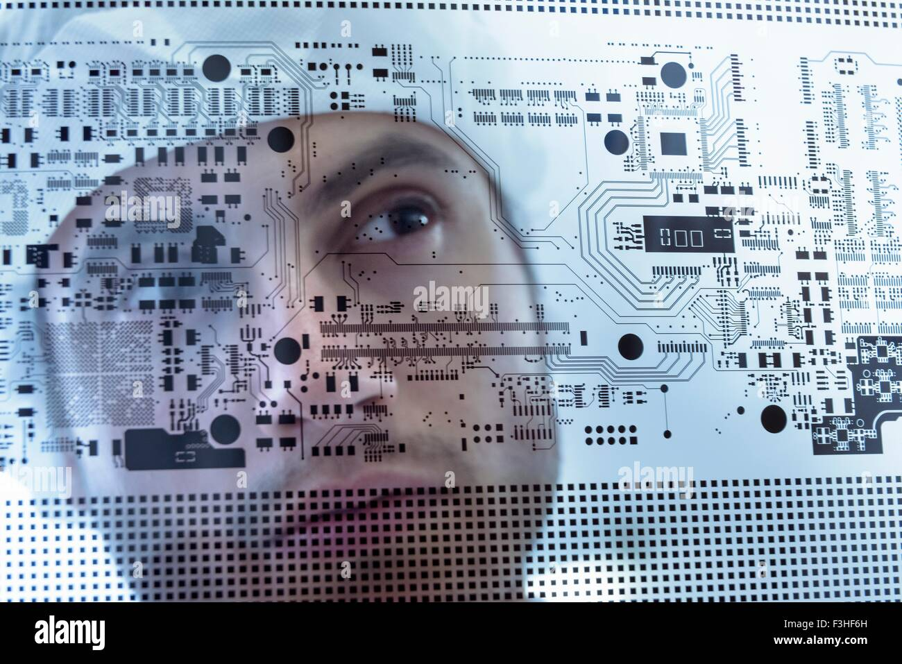 Worker inspecting circuit board negative sheet in circuit board factory, close up - Stock Image