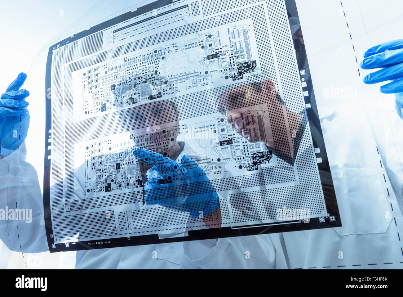 Workers inspecting circuit board negative sheet in circuit board factory Stock Photo