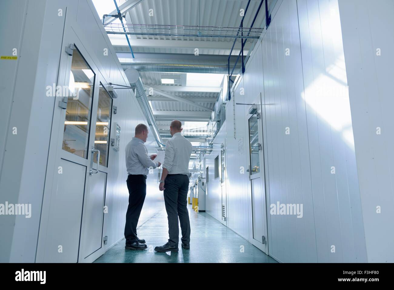 Managers inspecting robotic spray booths in automotive parts spray paint factory - Stock Image