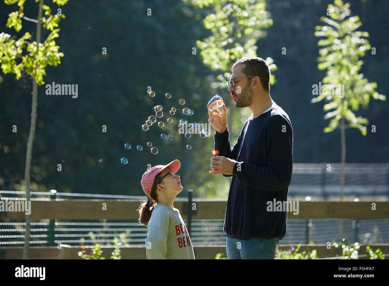 Man blowing bubbles as daughter looks up - Stock Image