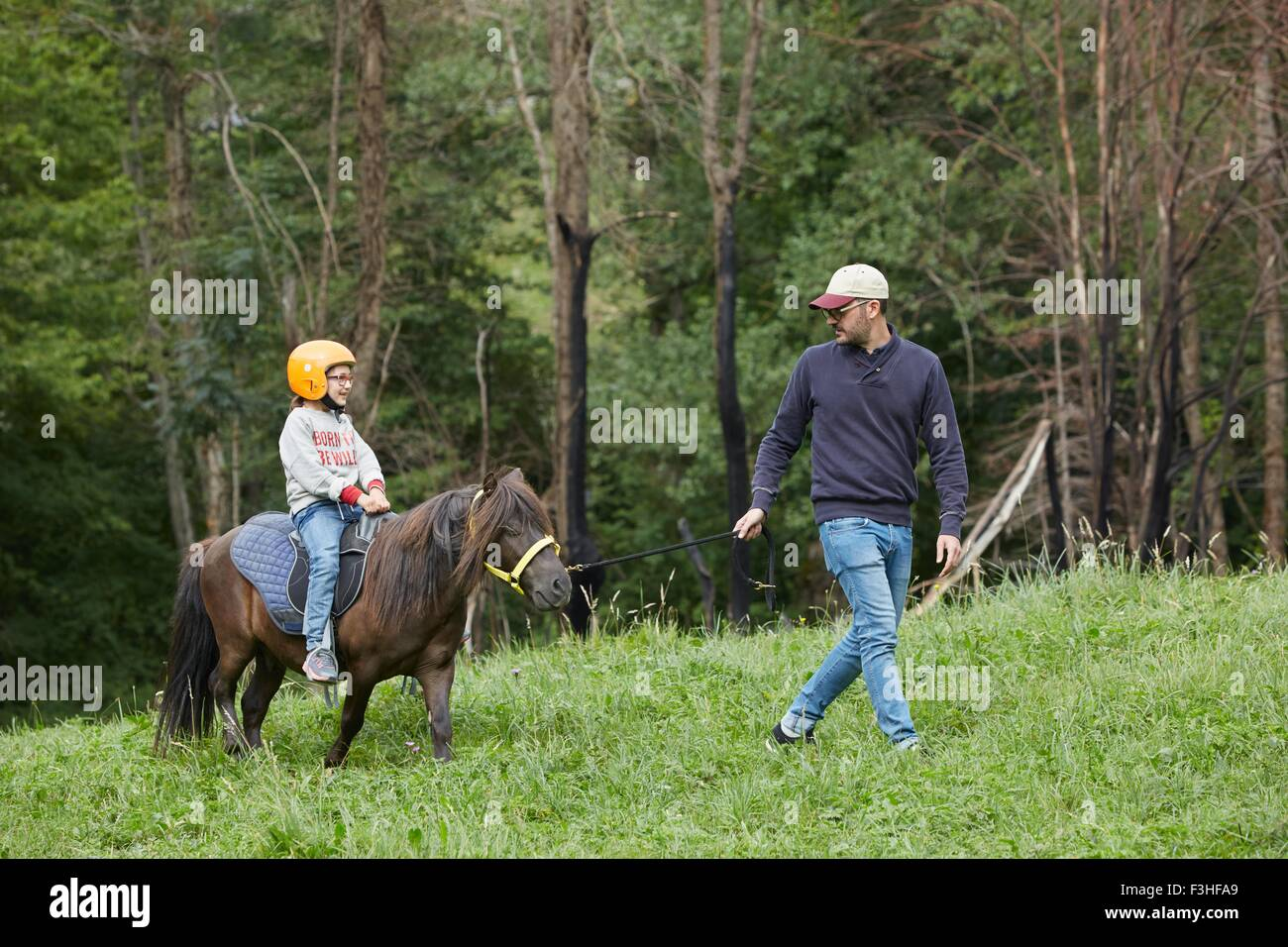 Father with daughter riding pony, Valle de Aran, Spain - Stock Image