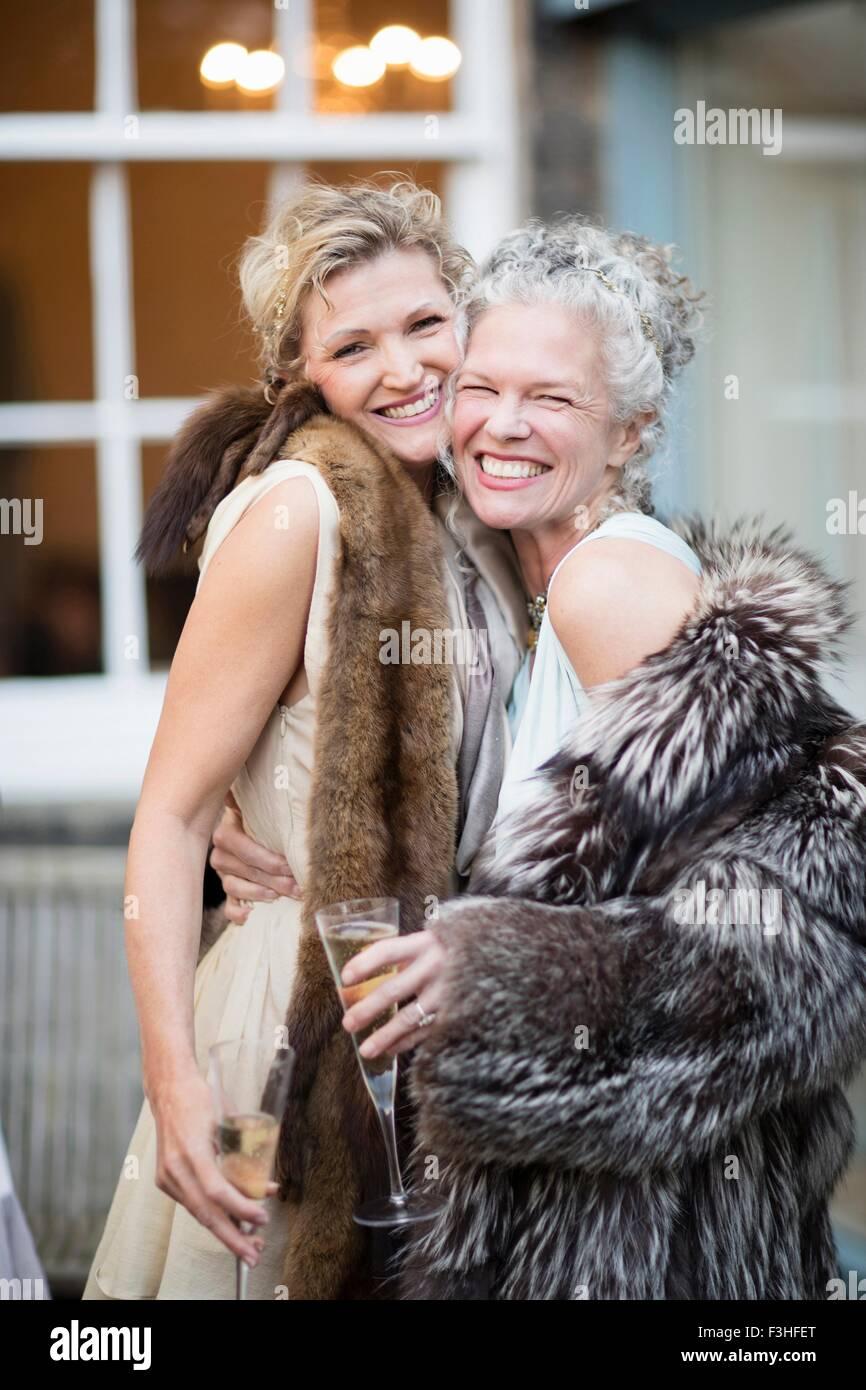 Elegant mature women enjoying champagne in urban garden - Stock Image