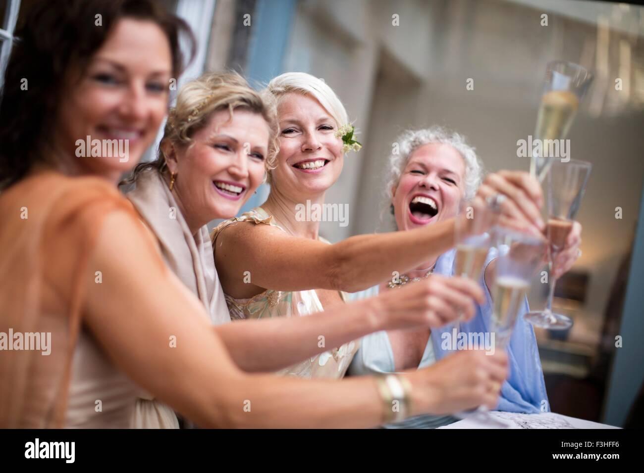 Elegant mature women toasting in urban garden - Stock Image