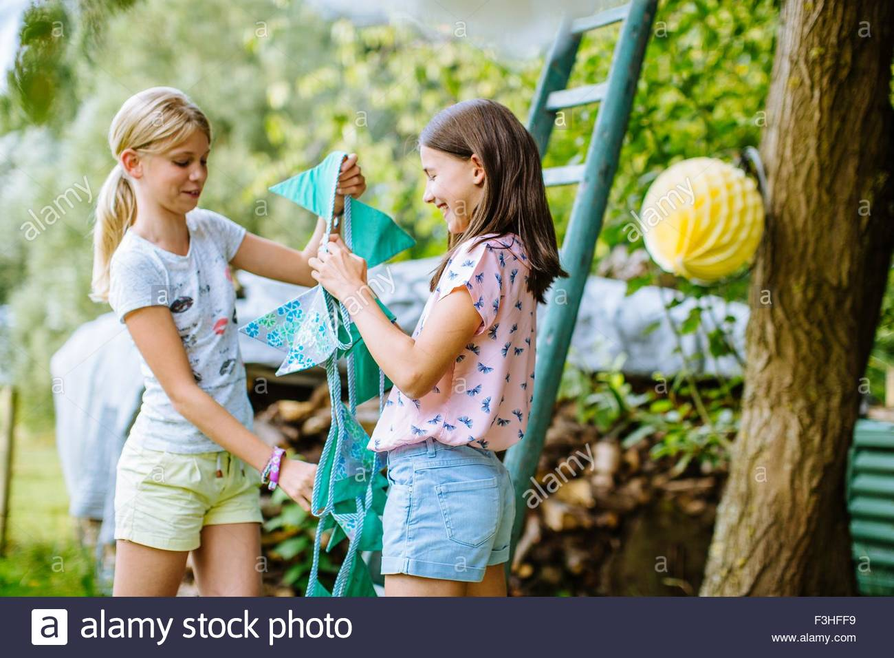 Girls decorating garden for summer party - Stock Image