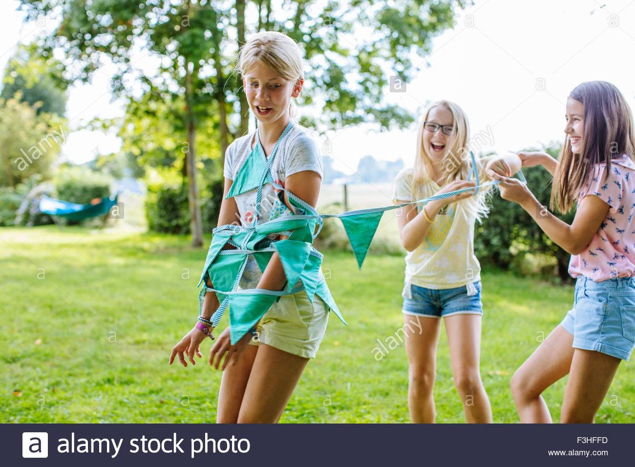 Girls wrapping friend up in bunting - Stock Image
