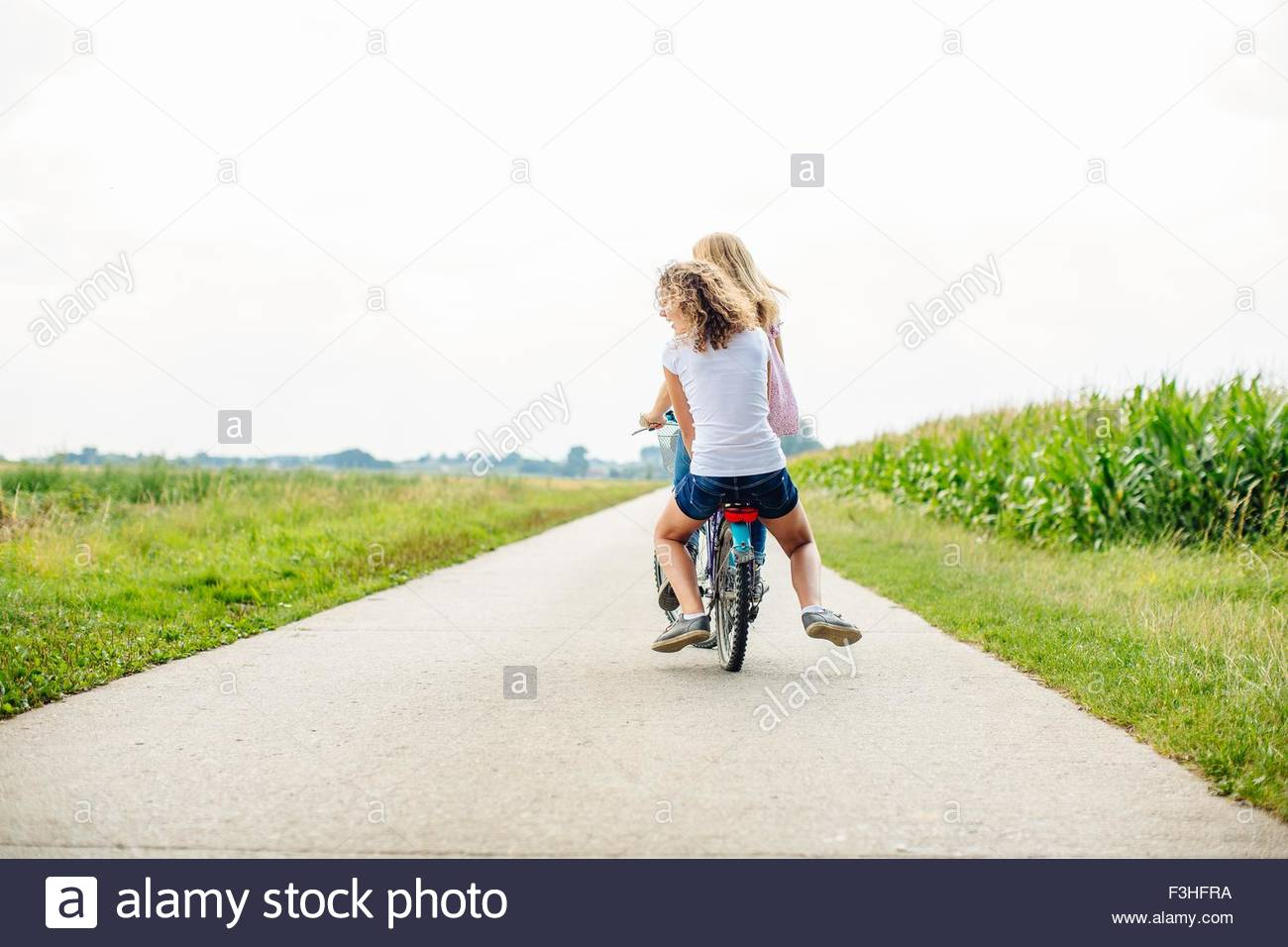 Rear view of two tween girls cycling along rural road - Stock Image