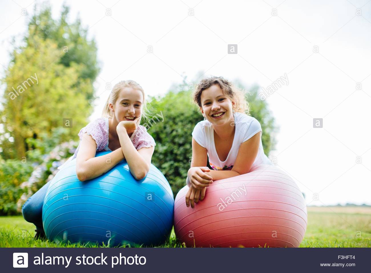 Portrait of two tween girls on exercise balls in garden - Stock Image