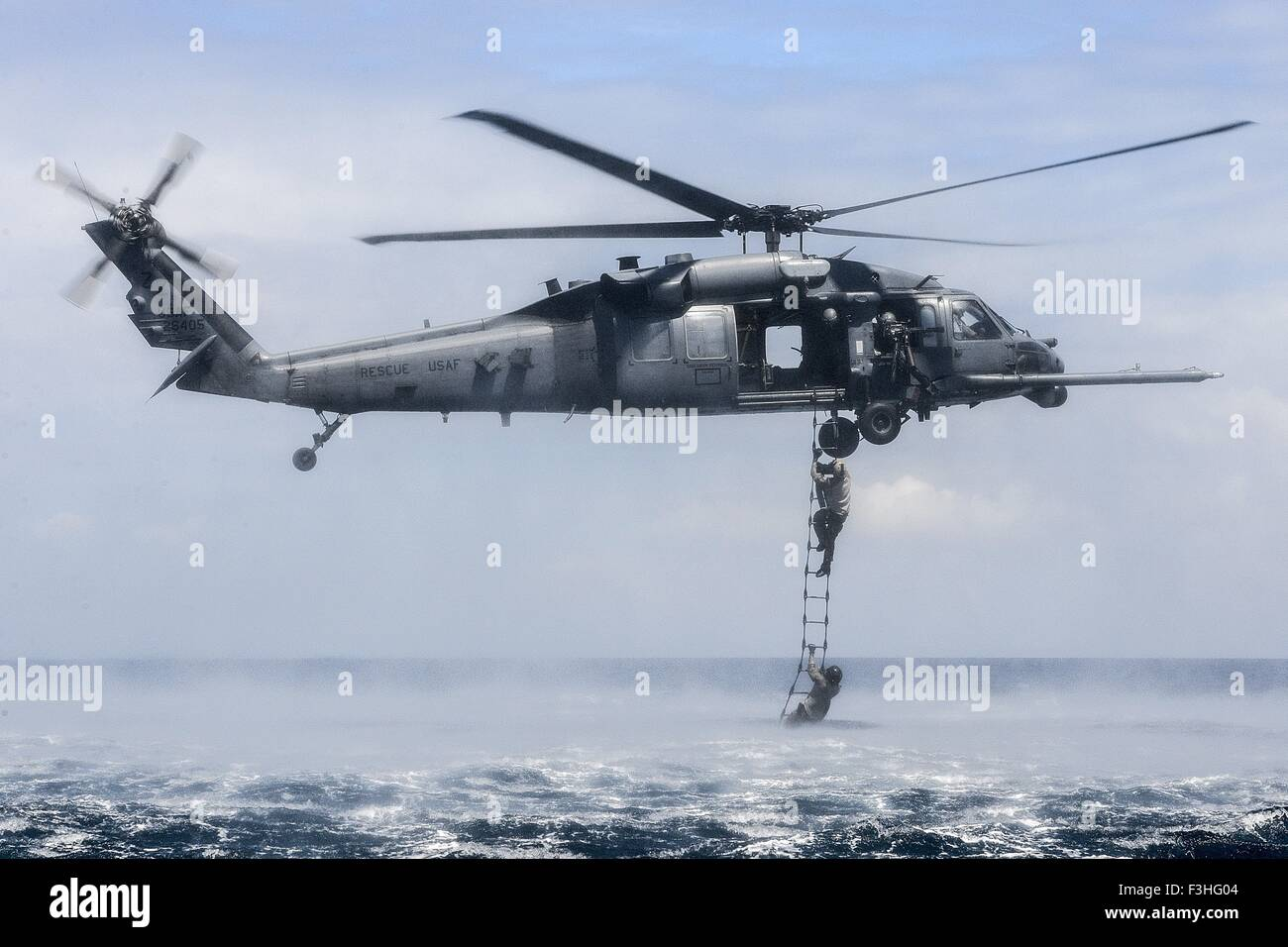 U.S. Air Force special forces rescue commandos jump from a HH-60G Pave Hawk helicopter into the ocean during amphibious - Stock Image