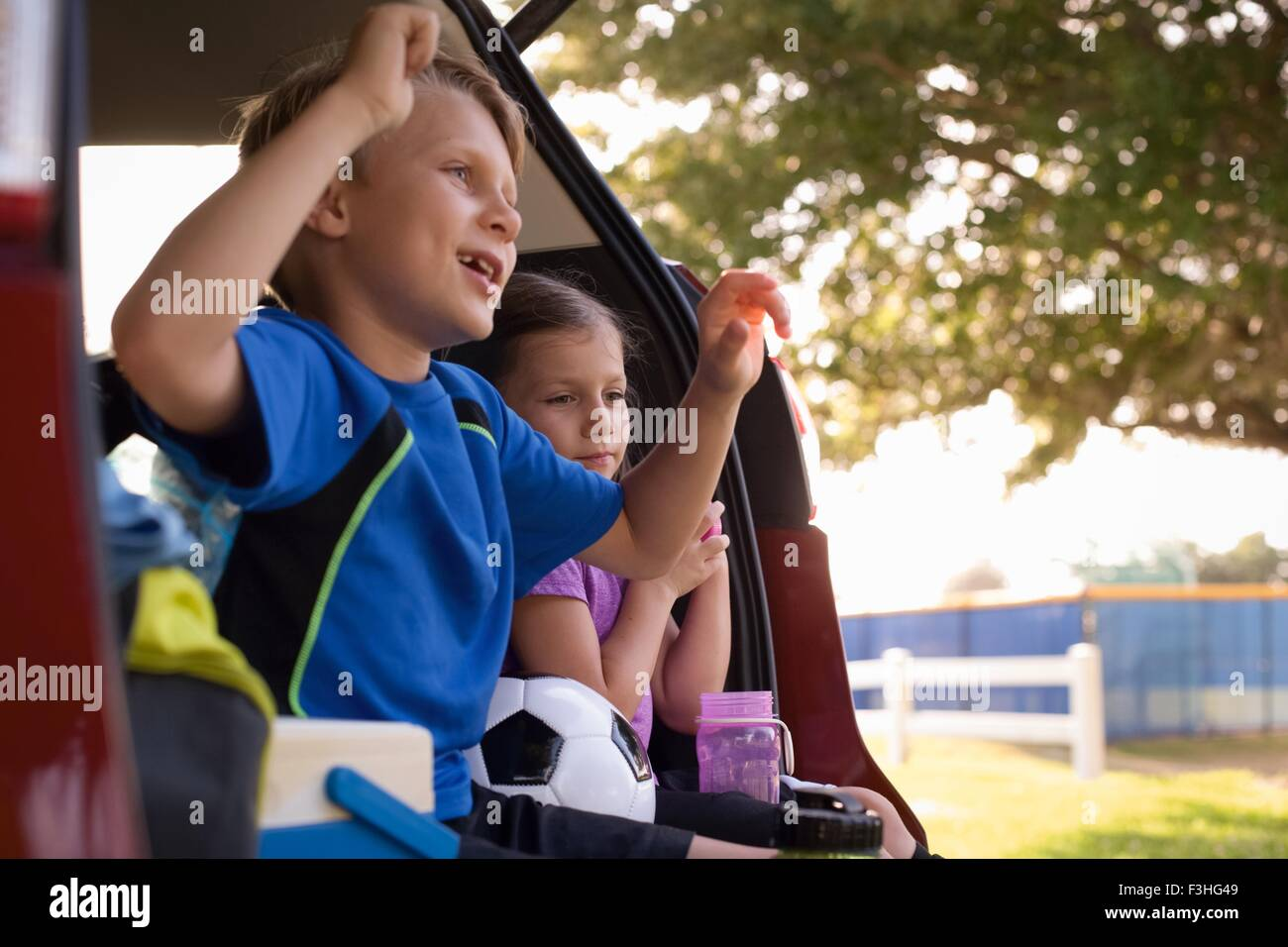 Boy and younger sister sitting in car boot watching football - Stock Image