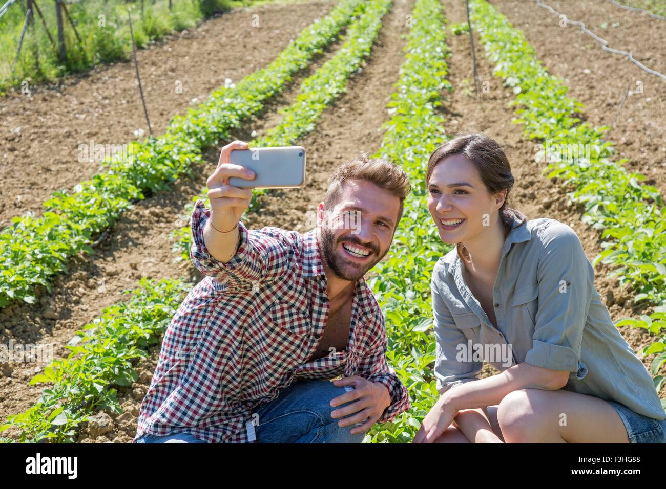 Young couple crouched in vegetable garden using smartphone to take selfie - Stock Image