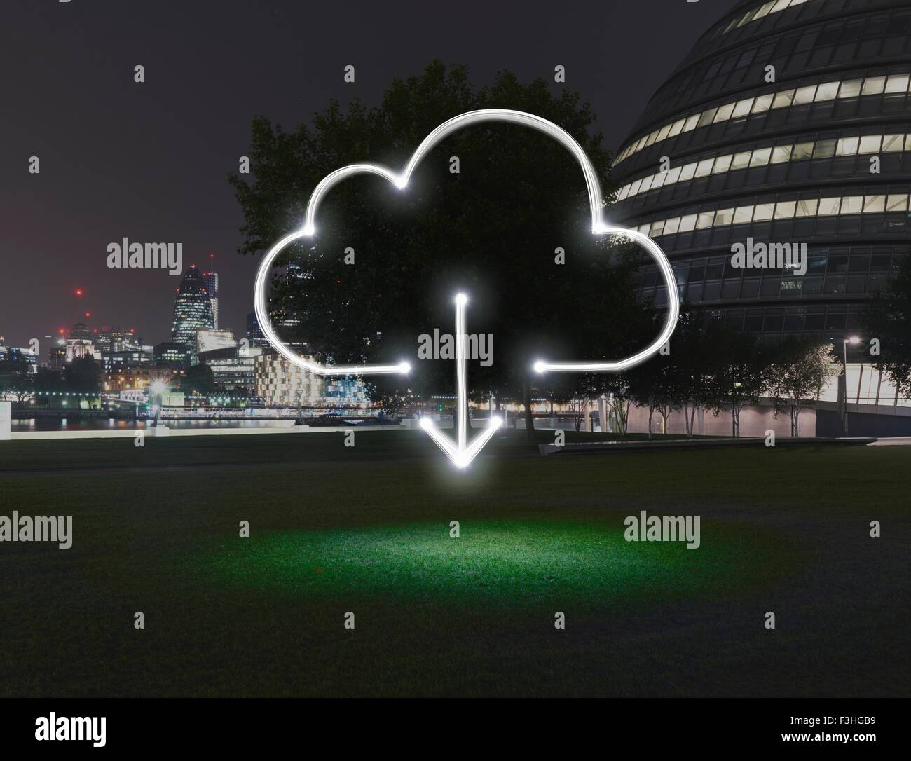 Glowing cloud symbol with download arrow in city at night - Stock Image