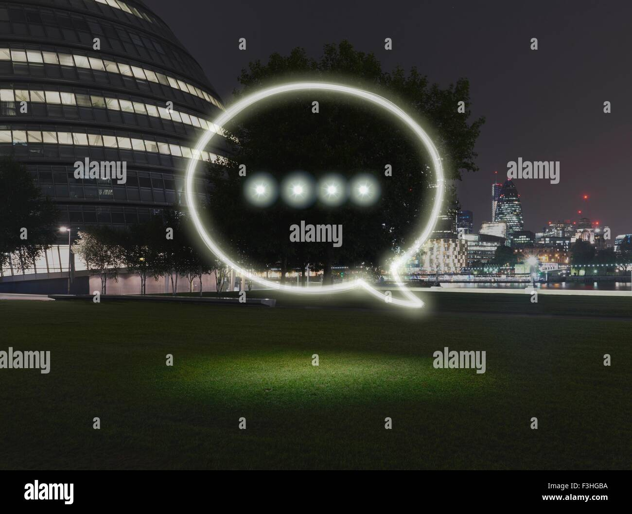 Glowing speech bubble symbol in city at night - Stock Image