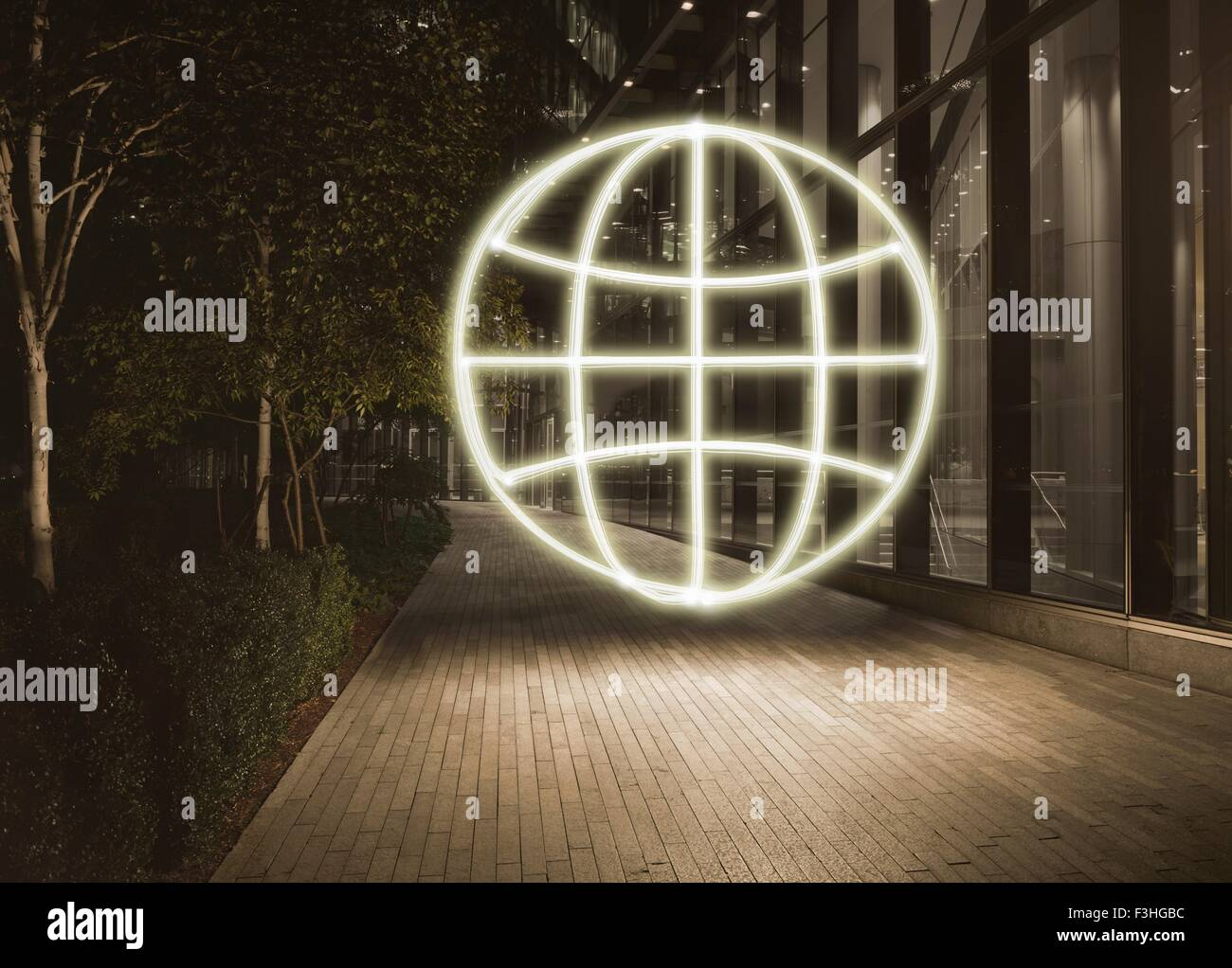 Glowing globe symbol in city at night - Stock Image