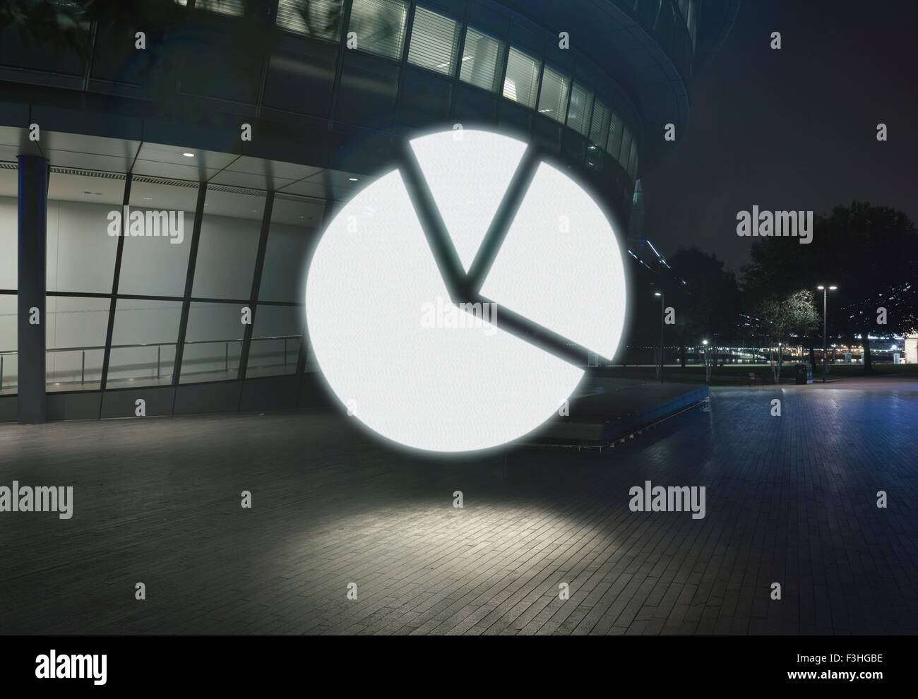 Glowing pie chart symbol in city at night - Stock Image