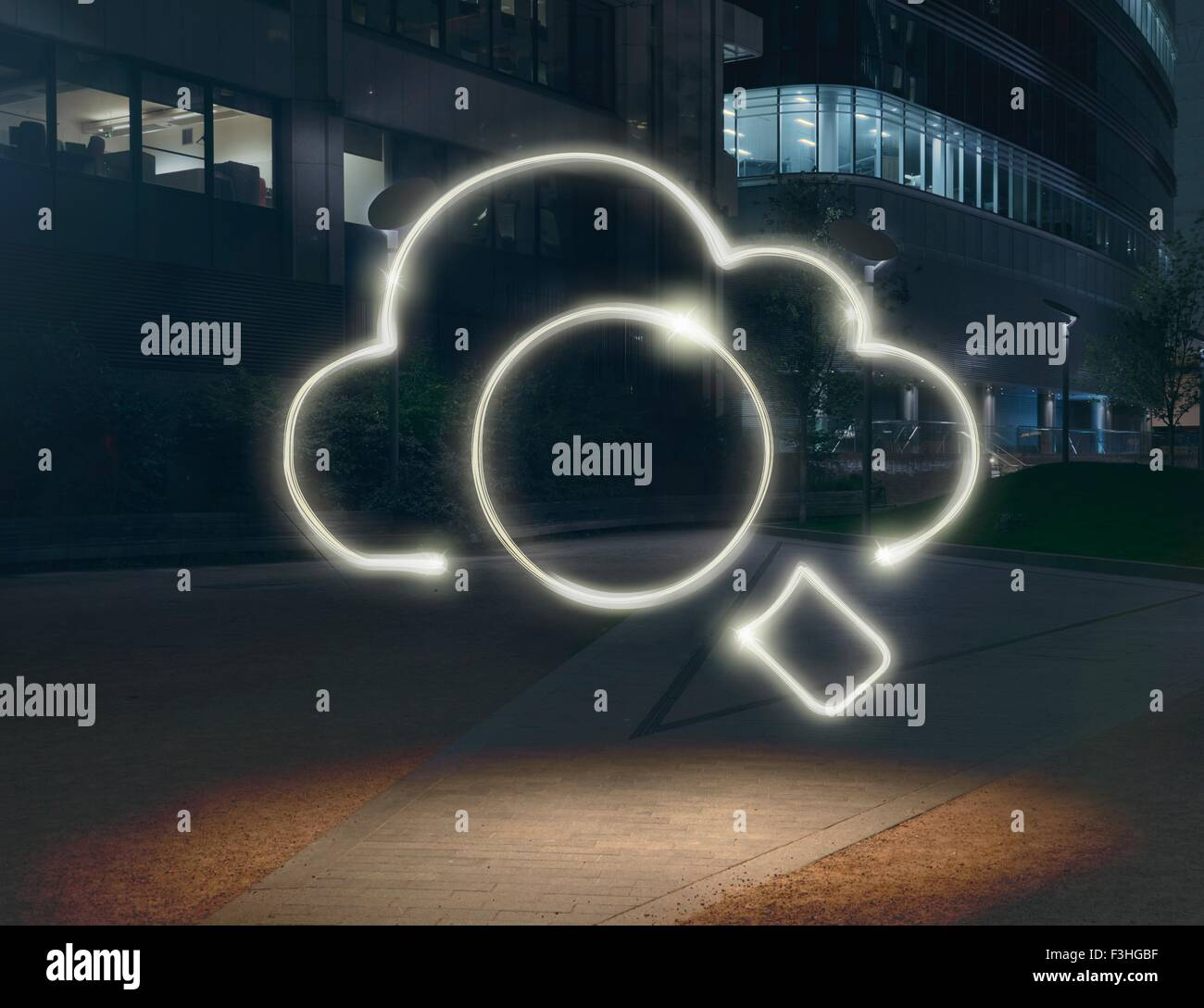 Glowing cloud symbol surrounding circle in city at night - Stock Image
